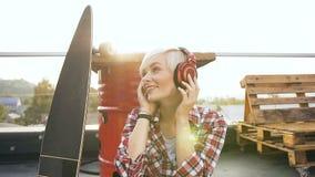 Fille blonde mignonne dans des écouteurs rouges écoutant la musique et la danse La jeune femme de hippie avec des écouteurs danse clips vidéos