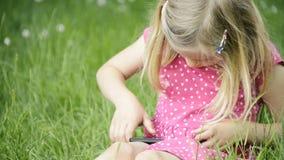 Fille blonde mignonne dans l'âge préscolaire se reposant dans l'herbe verte jouant avec le téléphone intelligent clips vidéos