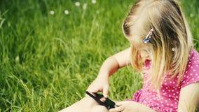 Fille blonde mignonne dans l'âge préscolaire se reposant dans l'herbe verte jouant avec le téléphone intelligent banque de vidéos