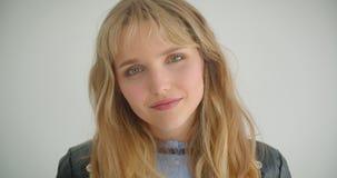 Fille blonde mignonne dans la veste en cuir souriant joli dans la caméra étant rêveuse et brillant d'isolement sur le fond blanc banque de vidéos
