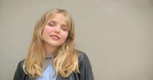 Fille blonde mignonne dans la veste en cuir souriant mystérieusement dans la caméra sur le fond gris de mur banque de vidéos