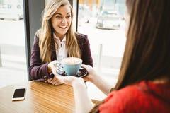 Fille blonde mignonne faisant servir un café par son ami Photographie stock
