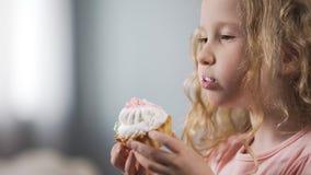 Fille blonde mignonne mangeant le gâteau crémeux, le risque malsain de casse-croûte, de carie et de diabétiques photographie stock libre de droits