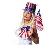 Fille blonde ondulant le petit drapeau américain d'isolement sur le blanc Images stock