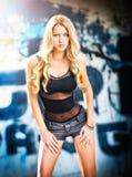 Fille blonde posant la mode près du mur de graffiti Image stock