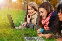 Fille blonde s'étendant avec l'ordinateur portatif Photographie stock libre de droits