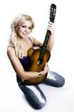 Fille blonde s'asseyant avec la guitare photo libre de droits