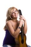 Fille blonde s'asseyant avec la guitare image libre de droits