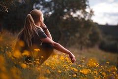 Fille blonde s'asseyant dans un domaine des fleurs jaunes photographie stock libre de droits