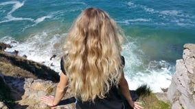 Fille blonde s'asseyant de retour sur la roche Images libres de droits