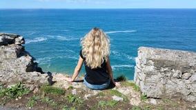 Fille blonde s'asseyant de retour sur la roche Photos stock