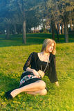 Fille blonde s'asseyant sur l'herbe Photographie stock