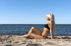 Fille blonde s'asseyant sur la mer de bleu de rivage Photos libres de droits