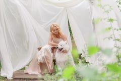 Fille blonde s'asseyant sur la rue avec un chien blanc dans des ses bras Images stock