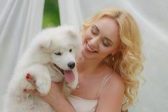 Fille blonde s'asseyant sur la rue avec un chien blanc dans des ses bras Photographie stock libre de droits