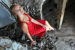 Fille blonde s'asseyant sur le bord dans la construction abandonnée Photographie stock libre de droits