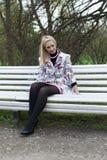 Fille blonde s'asseyant sur un banc de stationnement Photographie stock libre de droits