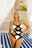 Fille blonde se tenant dans des maillots de bain d'une seule pièce noirs et blancs Images libres de droits
