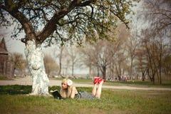 Fille blonde se trouvant sous un arbre avec le livre Photographie stock libre de droits