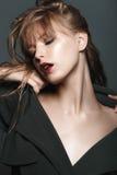 Fille blonde sexy avec les lèvres et l'or rouges sur les yeux dans un manteau foncé Images libres de droits