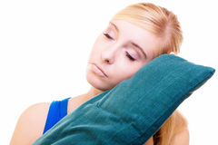 Fille blonde somnolente avec l'oreiller vert d'isolement au-dessus du blanc photographie stock