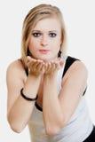 Fille blonde soufflant un baiser ou avec l'espace de copie en main Images stock