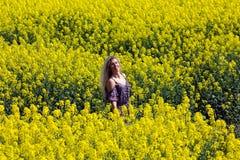 Fille blonde sur le gisement jaune de floraison de graine de colza Photos libres de droits