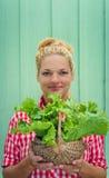 Fille blonde sur un fond de turquoise tenant le panier avec de la laitue Photographie stock
