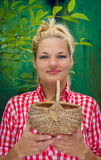 Fille blonde sur un fond vert tenant le panier Photographie stock