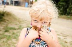 Fille blonde tenant de petits canards Photographie stock