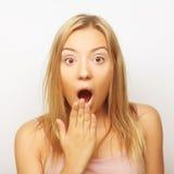 Fille blonde tenant sa tête dans la stupéfaction et ouvert-mout étonnés photographie stock libre de droits