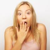 Fille blonde tenant sa tête dans la stupéfaction et ouvert-mout étonnés photo stock