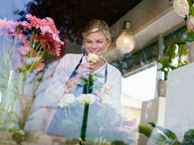 Fille blonde travaillant dans le système de fleurs Images stock