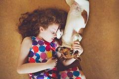 Fille bouclée étreignant un chiot et dormant sur le plancher en bois Photo stock