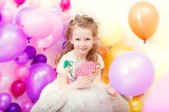 Fille bouclée adorable posant sur le contexte de ballons Image stock