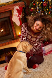 Fille bouclée avec le chien gentil dans la soirée de Noël photos stock