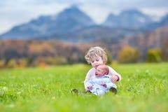 Fille bouclée mignonne d'enfant en bas âge et son frère nouveau-né de bébé jouant dedans Photographie stock libre de droits
