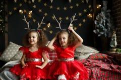 Fille bouclée mignonne de jumeaux s'asseyant sur le lit dans la pièce décorée de Noël, sur Noël égalisant l'arbre de sapin proche Photo stock