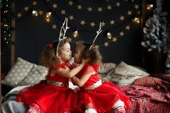 Fille bouclée mignonne de jumeaux s'asseyant sur le lit dans la pièce décorée de Noël, sur Noël égalisant l'arbre de sapin proche Image libre de droits