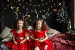 Fille bouclée mignonne de jumeaux s'asseyant sur le lit dans la pièce décorée de Noël, sur Noël égalisant l'arbre de sapin proche Images stock