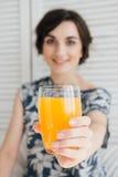Fille buvant du jus d'orange au petit déjeuner dans le lit Photos libres de droits