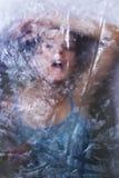 Fille cachée derrière configurations transparentes Photographie stock libre de droits