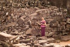 Fille cambodgienne dans des ruines se tenantes prêt de robe de Khmer de temple de Bayon dans la ville d'Angkor Photo stock