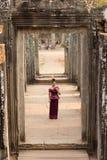 Fille cambodgienne dans la robe de Khmer se tenant dans le temple de Bayon dans la ville d'Angkor photos libres de droits