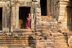 Fille cambodgienne dans la robe de Khmer se tenant dans une porte au temple de Bayon dans la ville d'Angkor Image libre de droits
