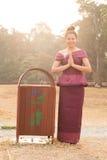 Fille cambodgienne dans la robe de Khmer se tenant prêt une poubelle Angkor Vat Image stock