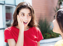 Fille caucasienne étonnée parlant avec l'amie Images libres de droits