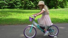 Fille caucasienne adorable avec des tours de chapeau sur la bicyclette en parc de ville Mouvement de cardan banque de vidéos