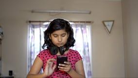 Fille caucasienne aisan indienne occupée au téléphone vérifiant l'écouteur des textes dans le cou Portrait de vue de face de mélo banque de vidéos