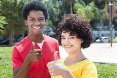 Fille caucasienne avec l'ami d'afro-américain montrant le pouce Images stock